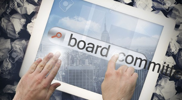 26807254-hand-touching-the-word-board-committees-on-search-bar-on-tablet-screen-on-crumpled-papers